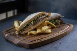 Porchetta sandwich served with fries
